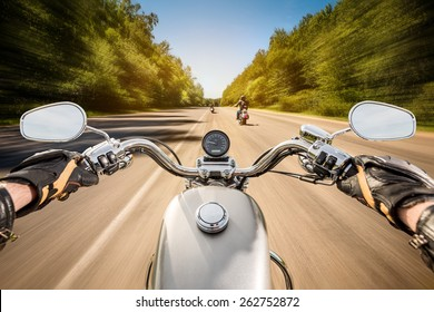 Biker driving a motorcycle rides along the asphalt road. First-person view.