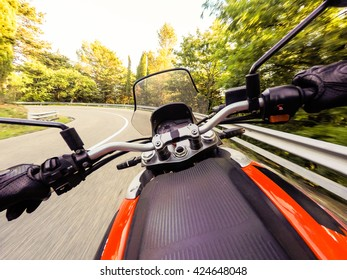 Biker driving a motorcycle rides along the asphalt road. First-person view