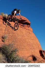 A biker drops down a steep sandstone face.