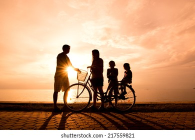 Biker family silhouette , family at the beach at sunset.