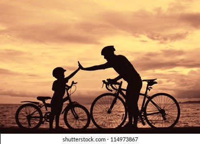 Biker family silhouette , daddy and son at the beach at sunset.