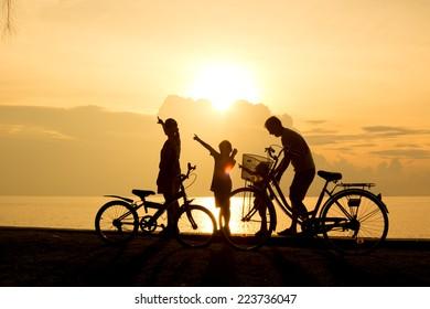 Biker family silhouette , family on the beach at sunset.