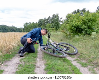 The biker fell from a bike to the grass. Bicycle accident. Biker lying on the road and holding his leg