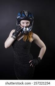 Biker girl in a beautiful black dress and helmet