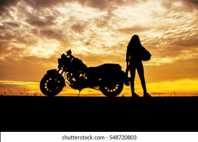 biker girl and classic motorcycle at sunset