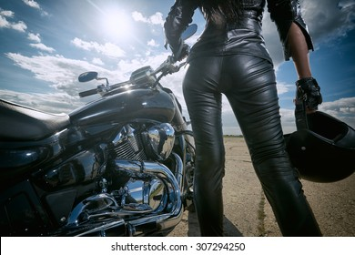 Biker girl in leather jacket standing by a motorcycle. Rear view
