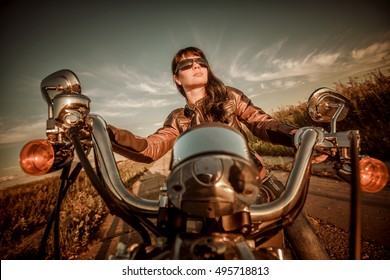 Biker girl with sunglasses sitting on motorcycle. Filter applied in post-production.