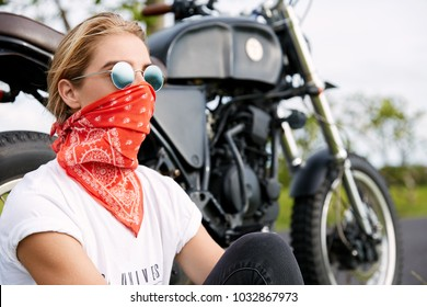 Biker girl in trendy shades, hides face with red bandana, sits near motorcycle, rides during sunny summer weather, enjoys wonderful nature and landscapes, has tour journey alone. Driving concept