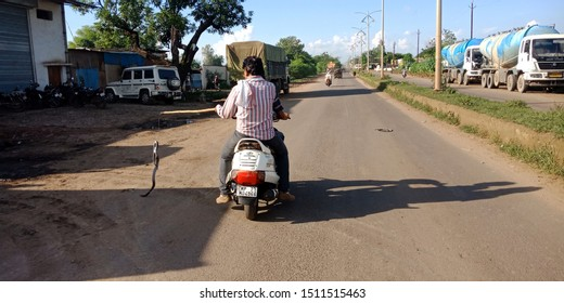 biker going with stick on hand with hanging snake on road at district Katni Madhya Pradesh in India shot captured on sep 2019