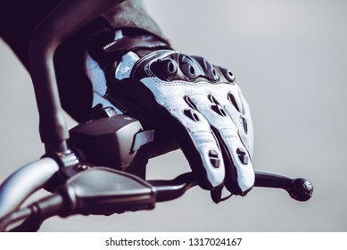 biker hand with protective glove in action riding on the road - safety and protection equipment on the road - toned with a trendy filter