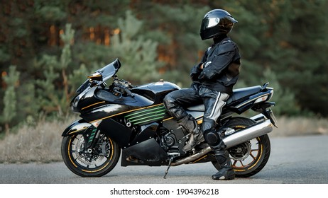 Biker in a helmet and leather protective equipment sits on a motorcycle, a sporty fast motorcycle