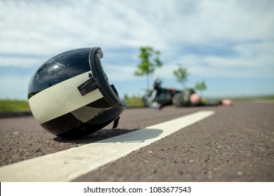 biker helmet lies on street near a motorcycle accident