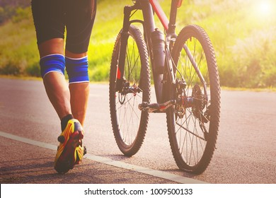 Biker with his flat bike tire,helping,exercise concept.