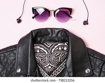 biker jacket and woman sunglasses with headphones on pink background. Alternative fashion set. Flat lay, top view