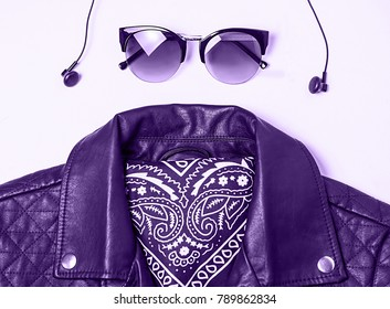 biker jacket and woman sunglasses with headphones on pink background. Alternative fashion set. Flat lay, top view. ultra violet color.