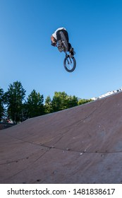 Biker jump high from jump box ramp performing dangerous 360 trick.