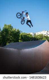 Biker jump high from jump box ramp performing dangerous superman trick.