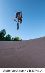 Biker jump high from jump box ramp performing 360 trick.