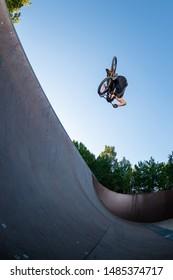 Biker jump high from jump box ramp performing flair trick.
