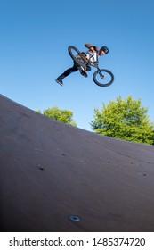 Biker jump high from jump box ramp performing foot off trick.
