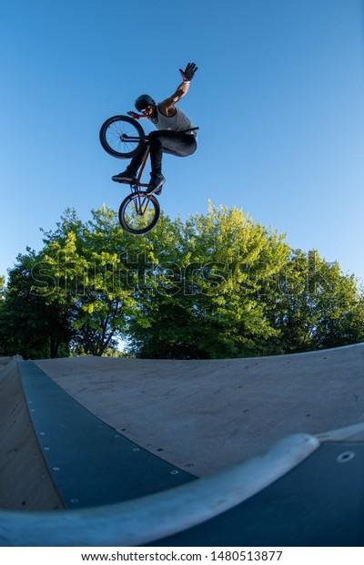 Biker jump high from jump box ramp performing hands off the handlebars trick.