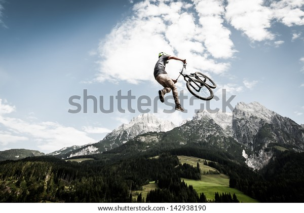 biker jumps a high stunt with mountains in the back