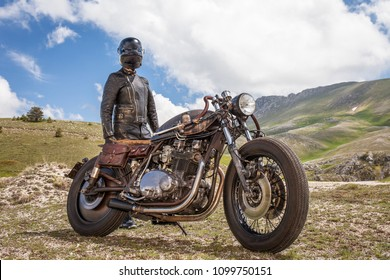 Biker with leather clothes and black mask stay with his custom rat motorcycle. Desolated mountain landscape.  Post apocalyptic concept