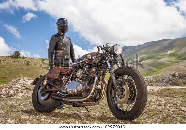Un motard avec des vêtements en cuir et un masque noir reste avec sa moto à rat sur mesure. Paysage montagneux déserté.  Concept post-apocalyptique