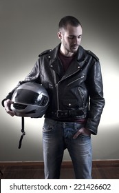 Biker in leather jacket posing holding his helmet