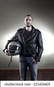 Biker in leather jacket posing holding his helmet