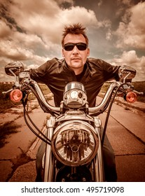 Biker in a leather jacket riding a motorcycle on the road. Filter applied in post-production.