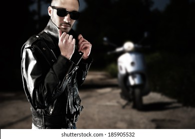 Biker in leather jacket and sunglasses posing with his scooter in an empty street