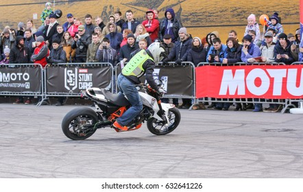 A biker lifting a motorcycle. St. Petersburg Russia - 15 April, 2017. International Motor Show IMIS-2017 in Expoforurum. Sports motorcycle show of bikers on the open area.
