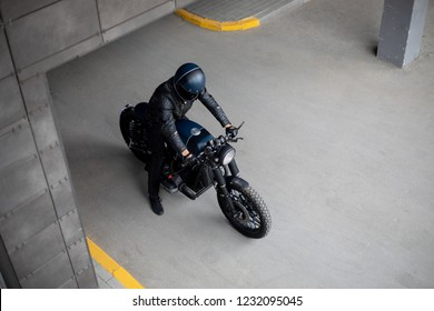 Biker man with Black blue rebuilt vintage custom motorcycle cafe racer in front of wall