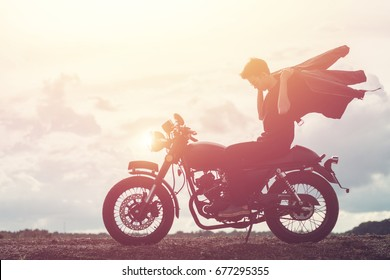 Biker man with his motorbike beside the natural and beautiful, enjoying freedom and active lifestyle, having fun on a bikers tour.sunset background and sky.