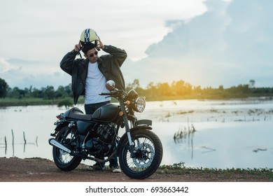 Biker man with his motorbike beside the natural lake and beautiful, enjoying freedom and active lifestyle, having fun on a bikers tour.sunset background and sky.