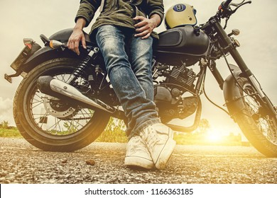 Biker man with his motorbike(motorcycle) on street and beautiful, enjoying freedom and active lifestyle, having fun on a bikers tour.