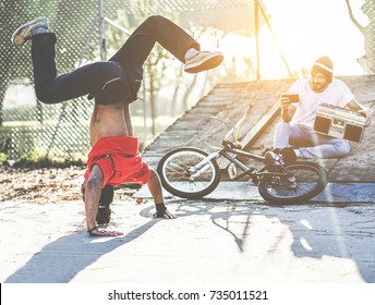 Biker man making video feed of his breakdancer friend dancing in city park outdoor - Young people having fun outdoor sharing media online - Focus on left man - Youth, trend and friendship concept