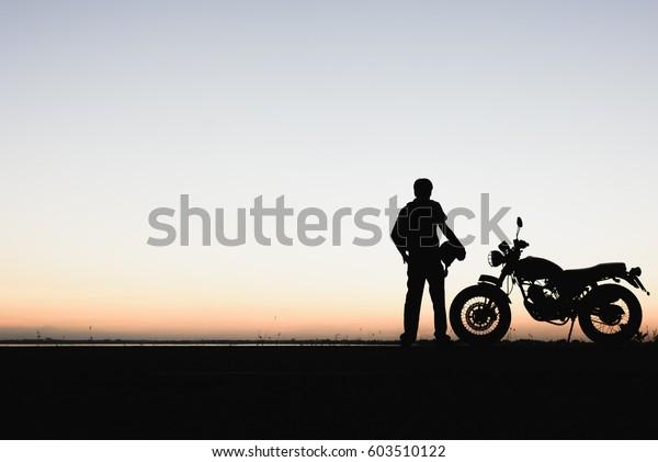 バイカーの男性とバイクの若い乗り手は、旅の間に、自然の光、夜間の空の光を見るために、トレンディのバイクを止めて休んでいた。シルエット壁紙のコンセプト