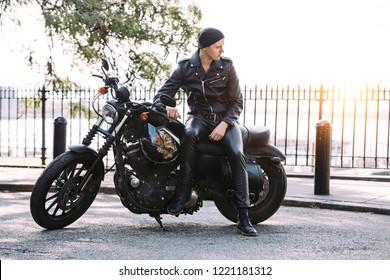 Biker man on black motorcycle parked on city street
