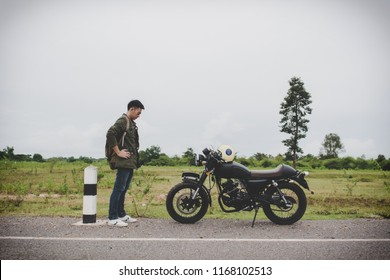 Biker man stand looking at his motorbike(motorcycle) on street and beautiful.