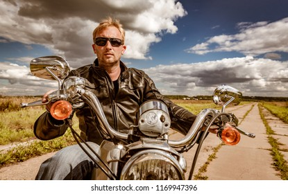 Biker man wearing a leather jacket and sunglasses sitting on his motorcycle