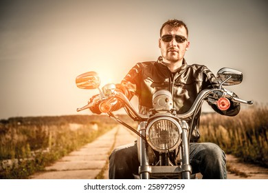 Biker man wearing a leather jacket and sunglasses sitting on his motorcycle looking at the sunset.