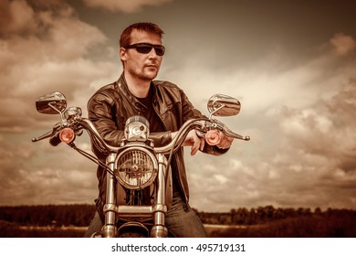 Biker man wearing a leather jacket and sunglasses sitting on his motorcycle. Filter applied in post-production.