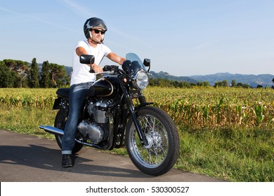Biker man wearing white t-shirt, blue jeans, helmet and sunglasses sitting on his vintage motorcycle looking at the sunset. Fashion portrait.