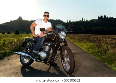 Biker man wearing white t-shirt, blue jeans and sunglasses sitting on his vintage motorcycle looking at the sunset. Fashion portrait.