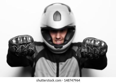Biker in motorcycle jacket and helmet imitate driving. Studio shot.