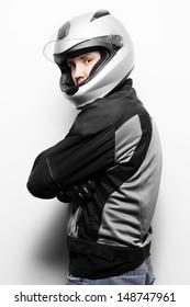 Biker in motorcycle jacket and helmet. Studio shot.