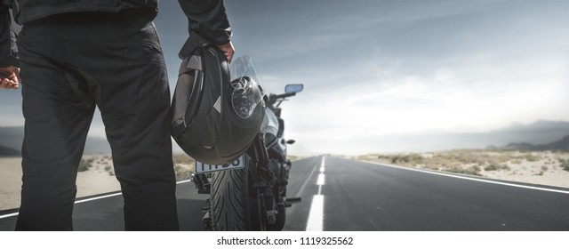 Biker with motorcycle on a country road