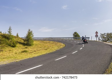 Biker on dangerous and winding road in the high mountains